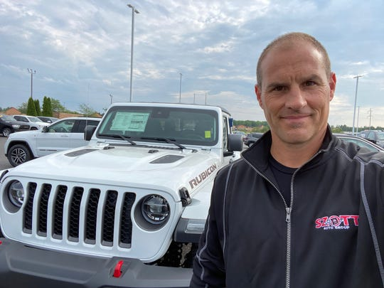 Thad Szott stopped by Feeny Chrysler Jeep Dodge Ram in Gaylord, Michigan, as he checked inventory levels around the state. Szott, co-owner of Szott Auto Group in White Lake Township, is pictured Monday beside a hot-selling new Jeep Gladiator pickup styled after the Wrangler. (Photo: Thad Szott)