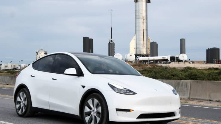 A man drives his Tesla car as the Starship SN8 of SpaceX is seen behind, days before a test launch of the company's new super heavy-lift Starship rocket from their facilities in this small town of Boca Chita, Texas, December 4, 2020. Gene Blevins | Reuters