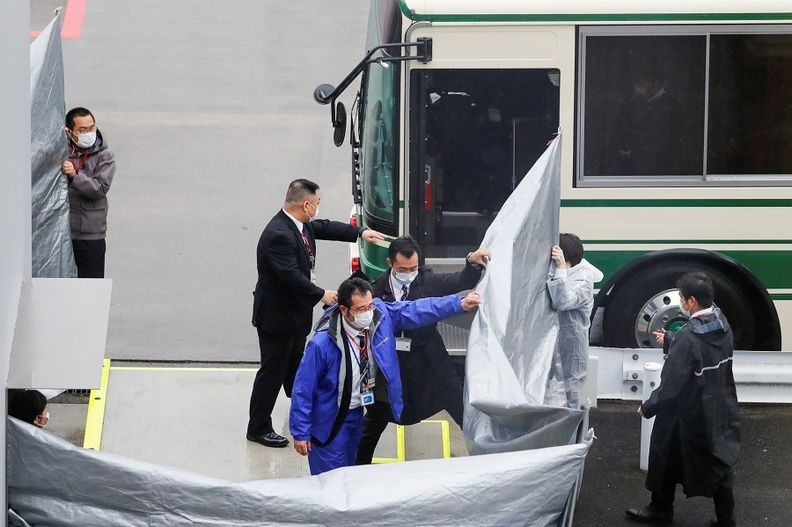 Japanese officers prepare to escort Michael Taylor and his son Peter Taylor after their arrival at Japan's Narita airport on March 2, following their extradition from the U.S REUTERS